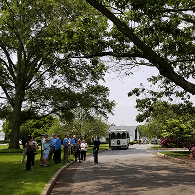 People gathered in the distance in front of trolly at 3rd annual arboretum tour