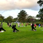 group of people doing yoga pose outside on grass